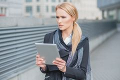 Woman holding a tablet standing thinking Stock Images