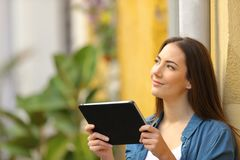 Woman holding a tablet thinking looking at side royalty free stock photography