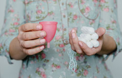Woman holding tampons and menstrual cup in hands Royalty Free Stock Images