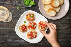 Woman holding tasty bruschetta with tomatoes. Over plate, top view Royalty Free Stock Photo