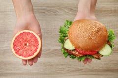 Woman holding tasty sandwich and half of fresh grapefruit Stock Image