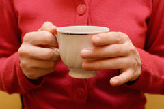 Woman holding a teacup in two hands Royalty Free Stock Photography