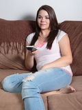 Woman holding television remote Stock Photo