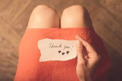 Woman holding a thank you note in her hand. Top view of a woman with pink dress holding a thank you note in her hand Stock Photos