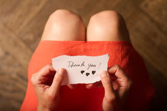 Woman holding a thank you note in her hand. Top view of a woman with pink dress holding a thank you note in her hand Royalty Free Stock Image