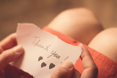 Woman holding a thank you note in her hand. Top view of a woman with pink dress holding a thank you note in her hand with shallow depth of field Stock Photo