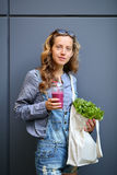 Woman is holding in their hands disposable cup with smoothies and bag with lettuce Stock Image