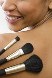 A woman holding three make-up brushes Royalty Free Stock Images