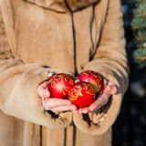 Woman holding  three red Christmas balls close-up Stock Photo