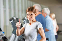 Woman holding thumb up in fitness Stock Photography