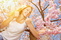 Woman holding thumbs up at cherry tree blossom Royalty Free Stock Images