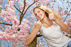 Woman holding thumbs up in spring Stock Image