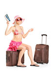 Woman holding a ticket seated on her baggage Royalty Free Stock Photo