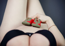 Woman holding a tiny baby shoes on her pregnancy belly Royalty Free Stock Image