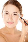 Woman holding a tiny cosmetic brush Royalty Free Stock Photos