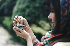 Woman holding a tiny doll and looking at it stock image