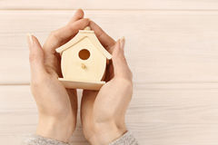 Woman holding tiny wooden house Royalty Free Stock Photos
