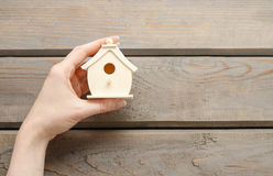 Woman holding tiny wooden house Royalty Free Stock Image