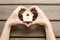 Woman holding tiny wooden house Royalty Free Stock Photo