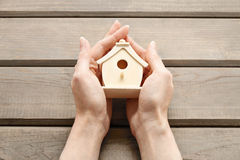 Woman holding tiny wooden house Royalty Free Stock Images