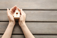 Woman holding tiny wooden house Stock Photography