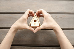 Woman holding tiny wooden house Stock Photos