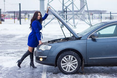 Woman holding on to the hood of her car Stock Images