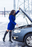 Woman holding on to the hood of her car and casually looking at the engine Royalty Free Stock Images