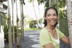 Woman Holding On To Palm Tree. Smiling young African American woman holding on to palm tree Stock Photography