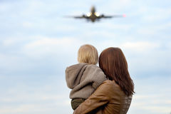Woman holding toddler with airplane on background. Young mother holding hes toddler son with airplane on background Royalty Free Stock Photo