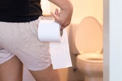 Woman holding toilet paper and using bathroom in morning. Pants is hanging on her legs Royalty Free Stock Photography
