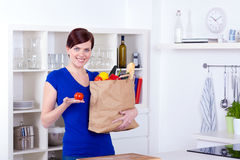 Woman holding a tomato and shopping bag Royalty Free Stock Photos