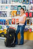 Woman Holding Tool Case In Hardware Store Stock Photography