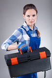 Woman holding a toolbox. Woman in work clothes with a toolbox Royalty Free Stock Photos