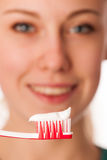 Woman holding toothbrush in front of teeth promoting mouth hygie Stock Image