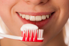 Woman holding toothbrush in front of teeth promoting mouth hygiene for healthy teeth. royalty free stock photo
