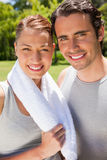 Woman holding a towel smiling with a man. Woman holding a towel around her neck smiling with a man Royalty Free Stock Photo