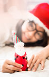 Woman holding  toy of Santa in hand Stock Photos