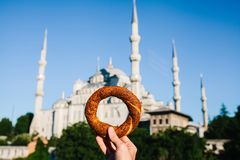 A woman is holding a traditional iretsky bagel named Simit in the background of the Blue Mosque in Istanbul, Turkey. Traditions, tourism Royalty Free Stock Images