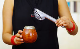 Woman holding traditional mate cup, addding sugar cube using other hand, south american herbal recreation drink Stock Image