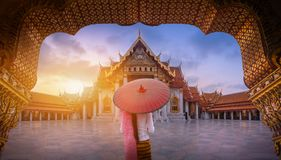 Woman Holding Traditional Red Umbrella On The Marble Temple, Wat Benchamabopitr Dusitvanaram At Sunrise In Bangkok, Thailand. Royalty Free Stock Photos