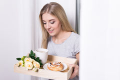 Woman holding tray with her breakfast at home Stock Image