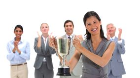 Woman holding a trophy with coworkers applauding Royalty Free Stock Photos