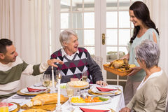 Woman holding turkey roast with family at christmas Royalty Free Stock Photos