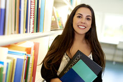 Woman holding two books in library Royalty Free Stock Photography