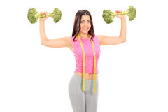 Woman holding two broccoli dumbbells Stock Photos