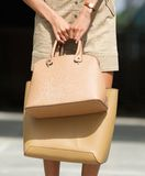 Woman holding two brown leather handbags Stock Photography