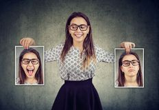 Woman holding two different face emotion masks of herself. Happy woman holding two different face emotion masks of herself royalty free stock photo