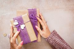 Woman holding two gifts boxes, rustic style stock image