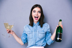 Woman holding two glass and bottle of champagne Stock Photos